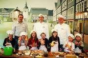 Stolz auf ihr selbst hergestelltes Gebäck: Einige der kleinen Bäckerinnen und Bäcker mit den Bäckermeistern (v. l.) Domenico Loparco, Holger Hassler und Michael Reinecke.