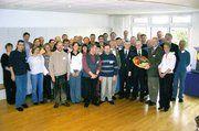 Auf dem Gruppenfoto, Senator Willi Lemke mit gebackener Schulranzen-Torte. Rechts daneben Heinrich Münsterjohann, Leiter des MeisterMarken Back- und Beratungszentrums.