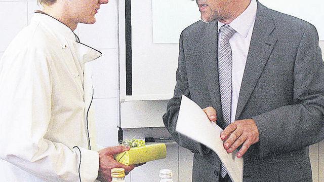 Schulleiter Anton Metz überreicht Felix Remmele zum Gewinn der Deutschen Meisterschaft der Bäckerjugend eine Urkunde.