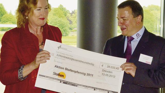 Landesobermeister Roland Ermer übergab Sigrid Winkler-Schwarz, Referentin für Grundsatzfragen des Diakonischen Werkes Sachsen, einen Spendenscheck über rund 28.000 Euro aus der Aktion Stollenpfennig 2011.  (Quelle: Salden)