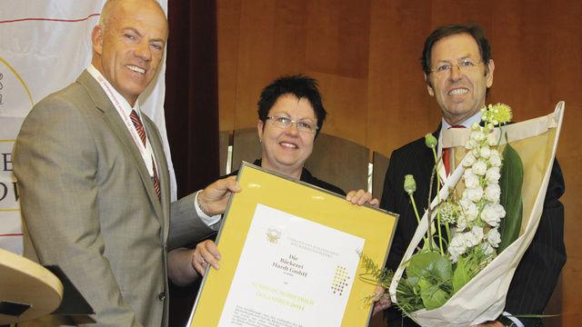 """Carmen Heincke (M.) nimmt von LIM Bernd Siebers (l.) und GF Walter Dohr die Auszeichnung als """"Ausbildungsbetrieb des Jahres"""" entgegen.  (Quelle: Heck)"""