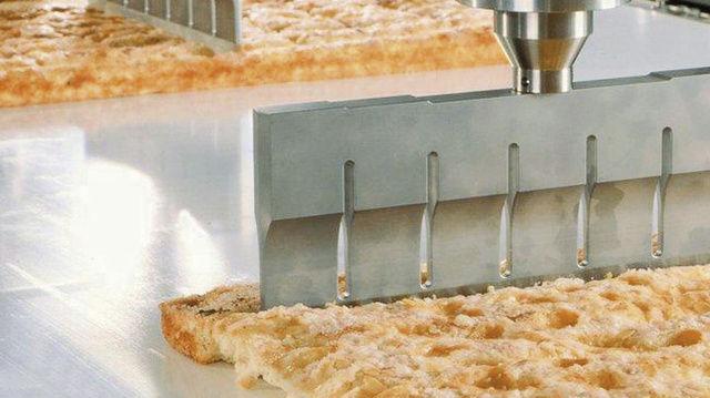 Die Ultraschall-Kuchenschneidemaschine von Döinghaus schneidet die Produkte freiliegend auf einem Transportband oder auf einer Schneideunterlage.