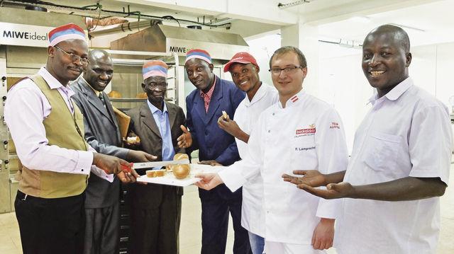 Pastor Idaki (links) und seine Kollegen freuen sich im Dezember 2014 über das erste frischgebackene Brot in der Angel Bakery. (Quelle: Backaldrin)