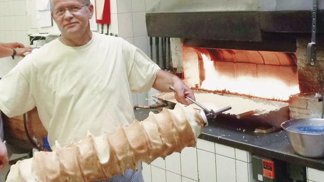 Meister Achim Lehnig mit einem frisch gebackenen Baumkuchen. (Quelle: Blath)