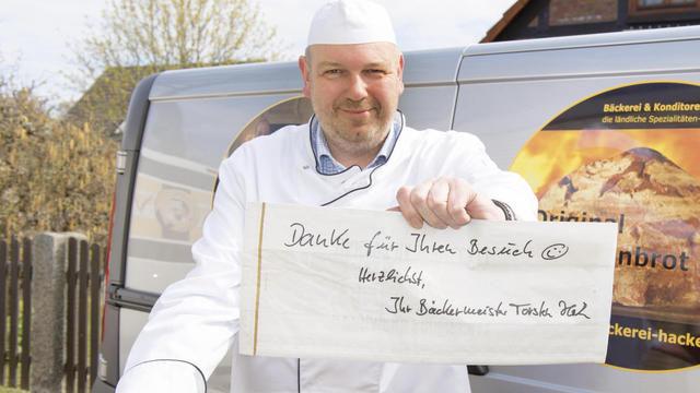Mit Brot, Schild und Humor: Torsten Hacke hat sich und damit sein Unternehmen zur Marke gemacht. (Quelle: Harald Winkler)