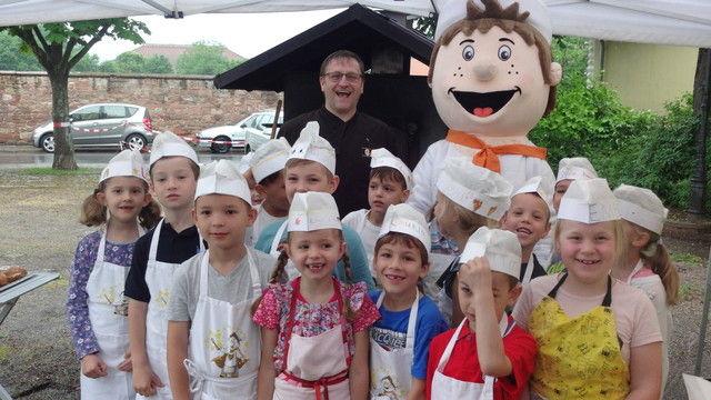 Claus Becker mit Maskottchen und begeisterten Kinder.  (Quelle: Zentralverband)