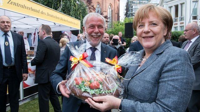 Michael Wippler, Präsident des Zentralverbands, überreicht Angela Merkel ein Brotpräsent. (Quelle: Foto: ZV)