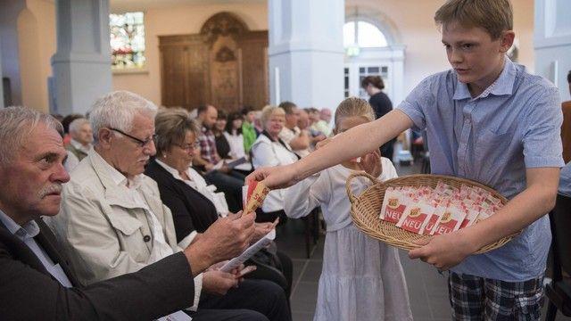 Kinder geben den Besuchern des Eröffnungsgottesdienstes Brot und sammeln Spenden. (Quelle: Rietschel(c)Brot für die Welt)