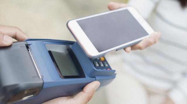 Einfach das Smartphone ans Lesegerät halten. So funktioniert bargeldloses Zahlen bereits in vielen Geschäften. (Quelle: Fotolia)