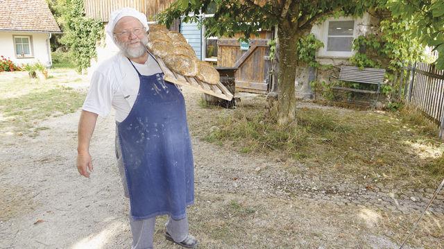 Günther Weber vor seiner Bäckerei (oben) und am Holzbackofen. Mit seinem Mitarbeiter Moritz Löser präsentiert er Roggen- und Dinkelvollkornbrot. (Quelle: Wolf)