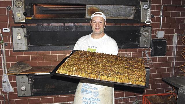 Georg Mair mit Pflaumenkuchen vor dem Steinbackofen. (Quelle: Filzek-Schwab)