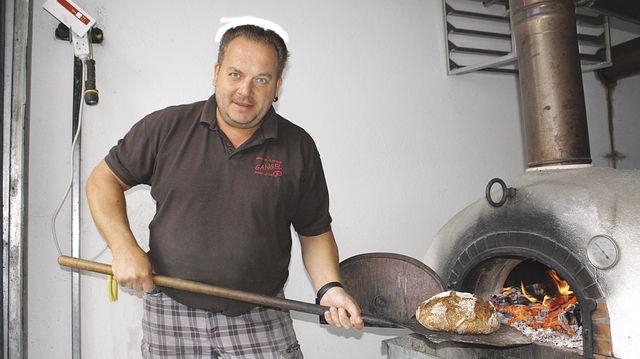 """Teamwork: Miguel Szczes backt die Brote im Holzofen, die Verena Gangel als """"Einzugsbrote"""" einpackt. (Quelle: Marconi)"""