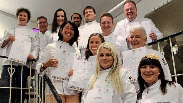Die ersten ausgebildeten Schokoladen-Sommeliers halten stolz ihre Auszeichnungen hoch. (Quelle: Akademie Deutsches Bäckerhandwerk Weinheim)