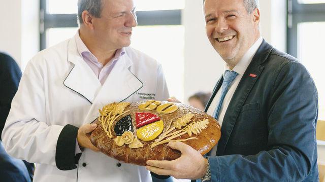 Roland Ermer (l.) und Dresdens Handwerkskammerpräsident Dr. Jörg Dittrich halten das Jubiläumsbrot. (Quelle: Verband)