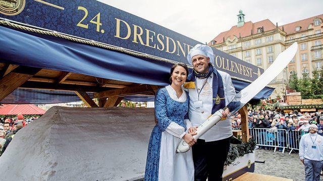 Das Stollenmädchen Hanna Haubold und Bäckermeister René Krause schneiden medienwirksam den Riesenstollen an. (Quelle: Verband/Michael Schmidt)