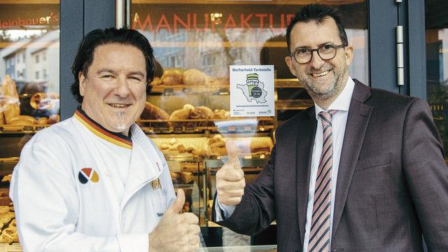 """Landesinnungsmeister Hans-Jörg Kleinbauer hat in seinem Café eine """"Becherheld-Tankstelle"""". Minister Reinhold Jost brachte den Aufkleber an. (Quelle: Bauer)"""