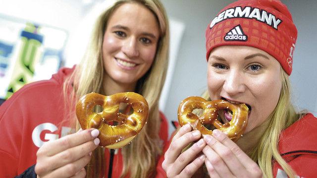 Medaillenstoff: Natalie Geisenberger (links), Olympiasiegerin im Rennrodeln, und die Zweitplatzierte Dajana Eitberger versorgen sich mit Brezeln. (Quelle: Hauke-Christian Dittrich (dpa))