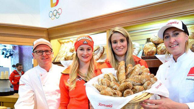 Goldmedaillen-Gewinnerin Natalie Geisenberger (2.v.r.) und Rennrodel-Teamkollegin und Silbermedaillen-Gewinnerin Dajana Eitberger (2.v.l.) mit Bäckermeister Hermann Lang und Konditormeisterin Petra Preinfalk. (Quelle: Picture Alliance)