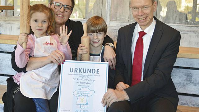 """Geschäftsführerin Heike Brinkhege hält mit Kindern die Urkunde für eine """"Familienfreundliche Gastronomie"""". (Quelle: Landkreis)"""