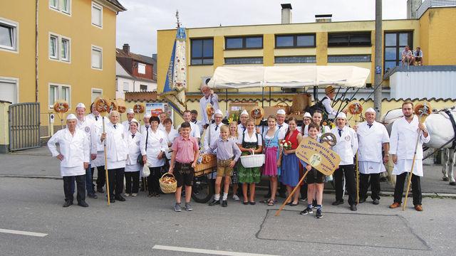 Mitglieder des Straubinger Fachvereins der Bäcker und Konditoren mit Fahne und geschmücktem Festwagen bei der Aufstellung vor dem Festzug zur Eröffnung des Gäubodenvolksfests in Straubing. (Quelle: Schuller)