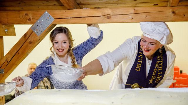 Stollenmädchen Lina Trepte und Fernseh-Konditorin Bettina Schliephake-Burchardt arbeiten am Riesenstollen. (Quelle: Michael Schmidt / Schutzverband Dresdner Stollen)