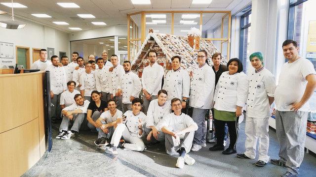 Das Lebkuchenhaus stand einen Monat lang in einer Bankfiliale von Elmshorn. Davor stehen seine Erbauer, angehende Bäcker und Fachverkäufer mit ihren Lehrern. (Quelle: Bernd Schauerte)