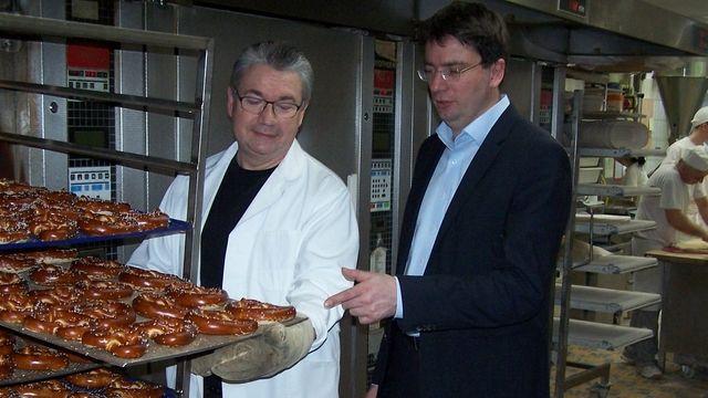 Heinz Hoffmann (links) zeigt Florian von Brunn, Verbraucherpolitischer Sprecher der SPD-Fraktion im Bayerischen Landtag, Verfahren zum Abbacken von belaugten Brezenteiglingen.  (Quelle: Verband)