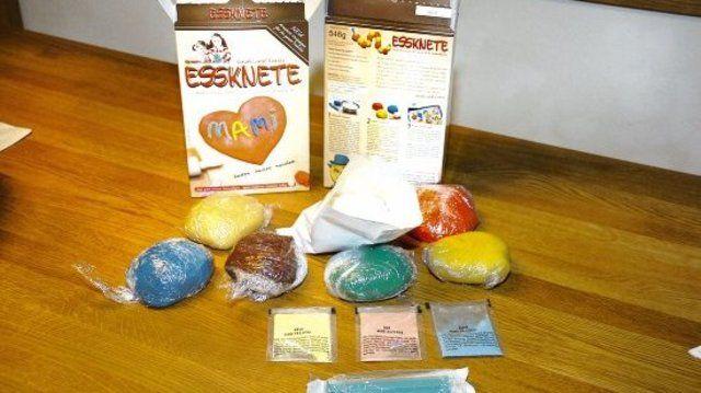 Eine Packung Essknete Vorder- und Rückseite, davor mehrere bereits gefärbte Knetekugeln, eine offene Tüte mit Grundmischung, die drei Farben und die Dosierspritze für die richtige Menge Wasser je Paket.