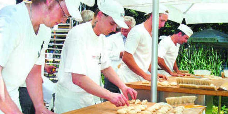 """Hitze sind Bäcker ja gewohnt, aber im """"Backofen"""" des Stadtparks Kempten kamen die Wettbewerbsteilnehmer beim Zöpfeflechten ganz schön ins Schwitzen."""