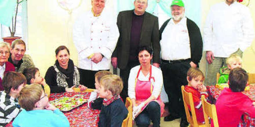"""Im """"Haus für Kinder"""" (von links): Obermeister Johann Grab, Stadtrat Otto Wickenhäuser, stellv. OM Wolfgang Frisch, Bäckermeister Hans Breitenstein mit der Leiterin der Ganztagesstätte inmitten der Kindergartenkinder."""