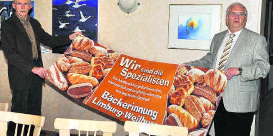 Bei der Jahreshauptversammlung der Bäckerinnung Limburg-Weilburg präsentierten Obermeister Winfried Laux (rechts) und Karl-Josef Roth stolz das neue Image-Banner, das auf die Innung und deren Betriebe aufmerksam machen soll. Foto: dt-press Foto: