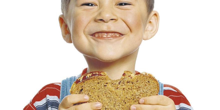 Herzhafter Biss in die Stulle: Der Verzehr von täglich drei Scheiben Brot gehört zur ausgewogenen Kinderernährung.