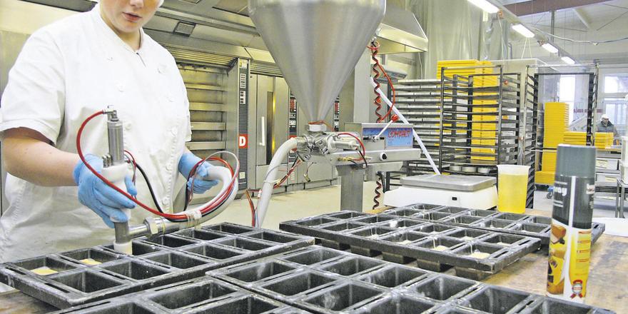 Konditorin Jeannine Helms portioniert die Sandmasse mit dem Unifiller Compact Power Lift, dessen Trichter zum Befüllen herabgelassen wird.