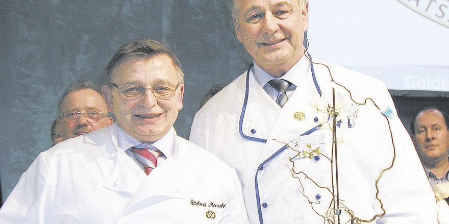 Zum 100-jährigem Bestehen des Unternehmens gratulierte Landesinnungsmeister Hans-Joachim Blauert (rechts) Bäcker- und Konditormeister Klaus Merschank mit einem Erinnerungspräsent.