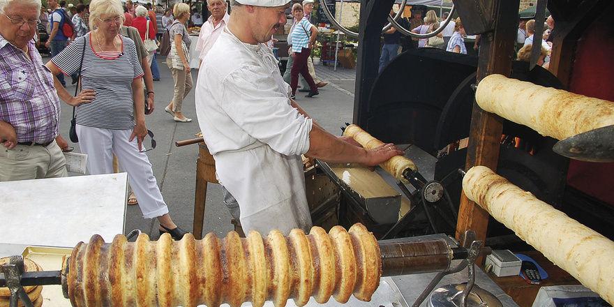 Durch das Backen über dem offenen Holzfeuer werden die Baumkuchen besonders saftig und bekommen ein unverwechselbares Aroma, was sie – neben ihrer äußeren Form – im doppelten Wortsinn zum Baumkuchen macht.