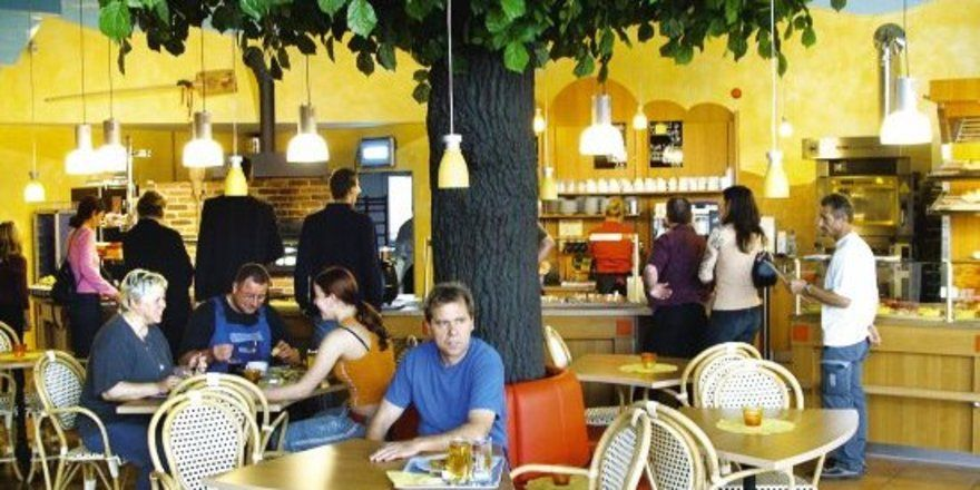 Einen Akzent von grüner Natur setzt der große künstliche Baum im Restaurant, unter dem die Gäste von Restaurant und Bäckerei sich entspannen können.