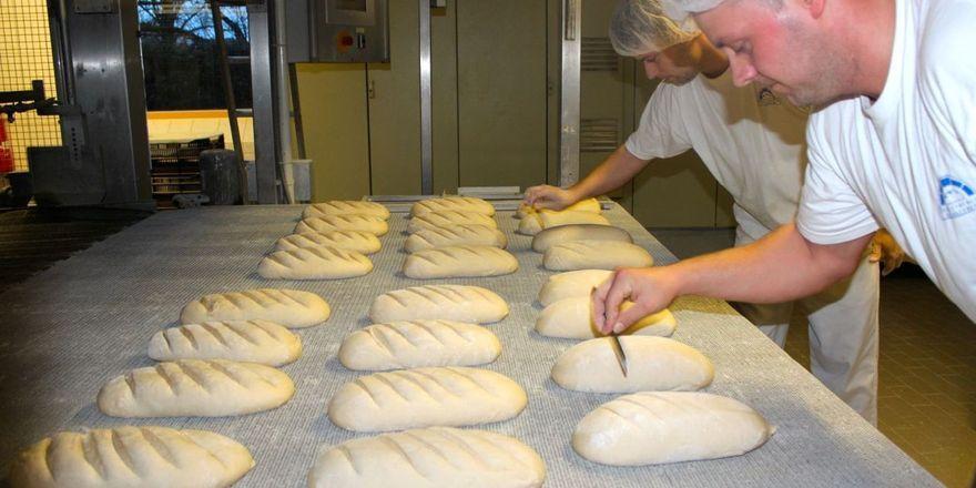Backvorbereitung: Miraldo Engel (vorne) und Christian Schwarz schneiden Brote.