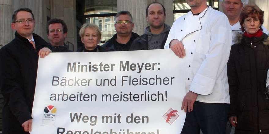 Bäcker-Obermeister Cord Buck (2. von rechts), Fleischer-Obermeister Eric Handke (links) und weiteree Branchenvertreter zeigen vor dem Landtag Flagge.