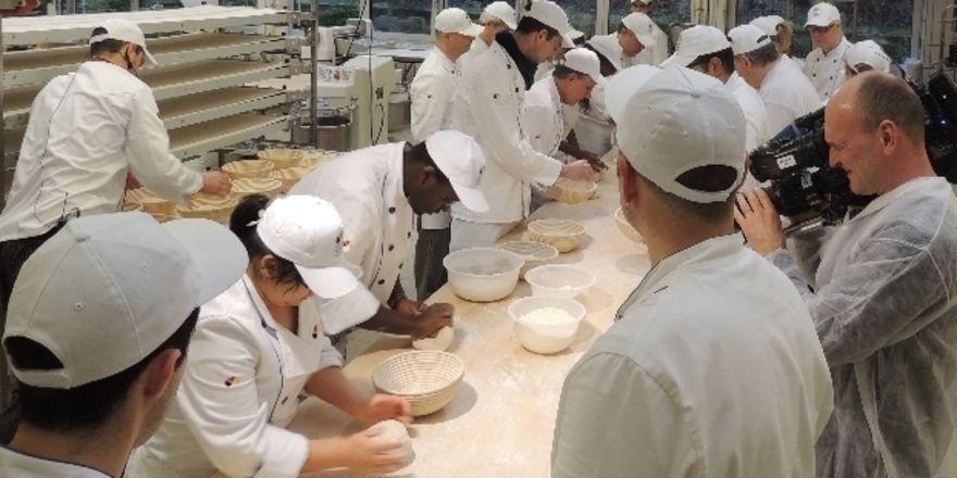 Dreharbeiten in der Backstube: 18 Teilnehmer aus fünf Kontinenten lernen in Weinheim, wie man deutsches Brot backt.