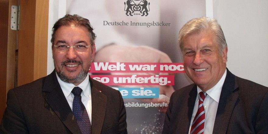"""ZV-Präsident Peter Becker (r.) und Hauptgeschäftsführer Amin Werner vor dem neuen Backzunft-Wappen """"Deutsche Innungsbäcker""""."""