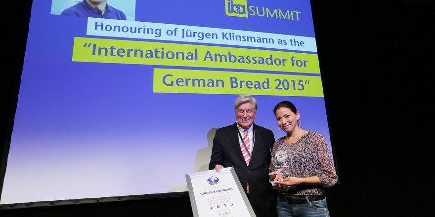 Noelia Vidalon von der Agapedia Stiftung nimmt stellvertretend für Jürgen Klinsmann die Auszeichnung von Peter Becker entgegen.
