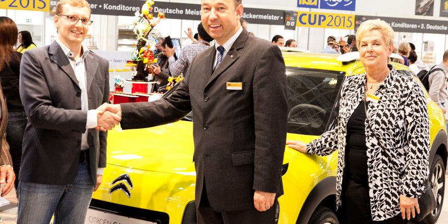 Friedemann Berg (Mitte) vom Zentralverband des Deutschen Bäckerhandwerks gratuliert Johannes Knoll, der für seinen Vater den Preis entgegenimmt.