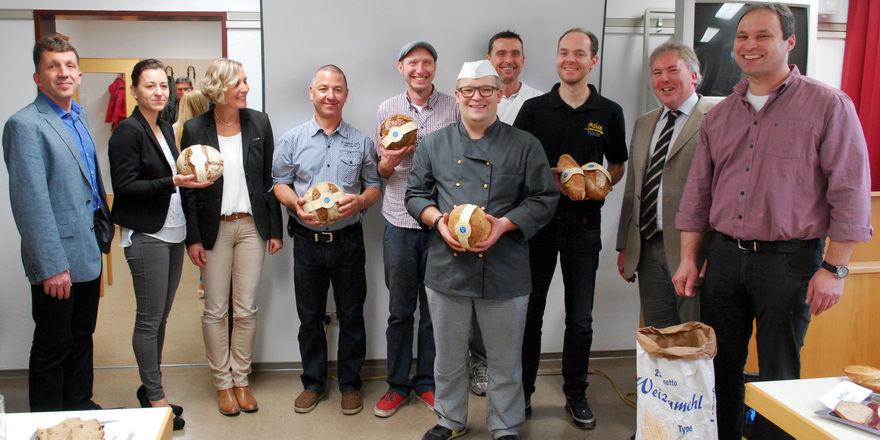 """Fünf der """"Grundwasserschutzbäcker"""" (Mitte) bei einer Präsentation ihres neuen Produkts mit entsprechender Banderole."""