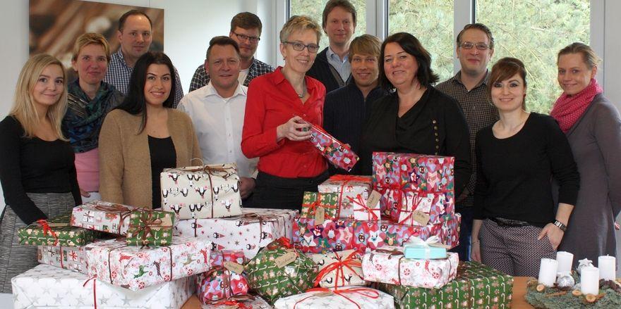Zusammen mit Kollegen überreicht Vandemoortele-Marketingleiterin Christina Herrmann (Mitte) die Geschenke an Jutta La Mura vom Verein Karlsson.