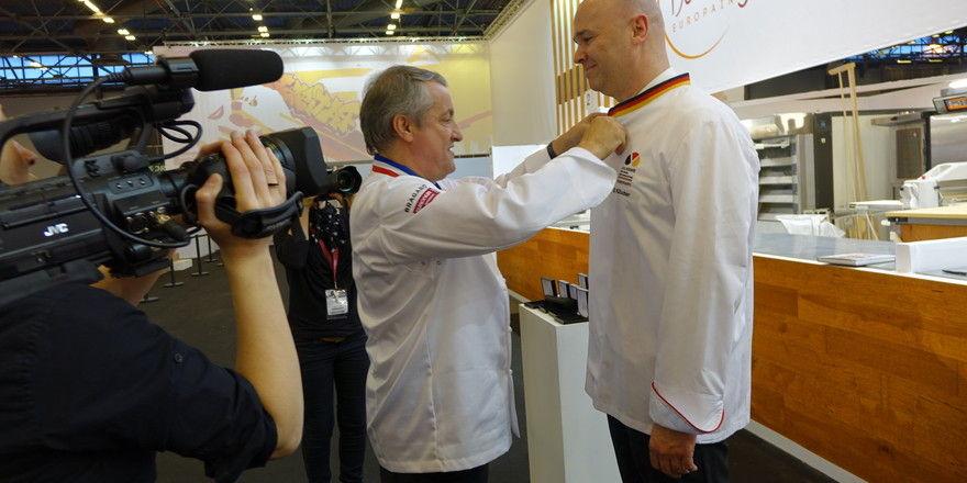 """Christian Vabret (von links) nimmt Bernd Kütscher in den Club """"Elite de la Boulangerie International"""" auf."""