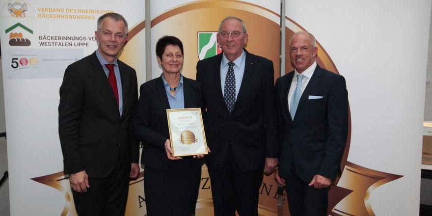 Johannes Remmel (links) übergibt Maria und Erich Lehnen die Auszeichnung Meister.Werk.NRW. Landesinnungsmeister des rheinischen Bäckerverbandes Bernd Siebers gratuliert dem Ehepaar zum Titel. Die Bäckerei ist eine von insgemsamt 32, die die Auszeichnung
