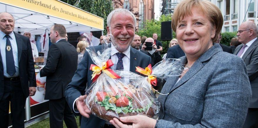 Michael Wippler, Präsident des Zentralverbands, überreicht Angela Merkel ein Brotpräsent.