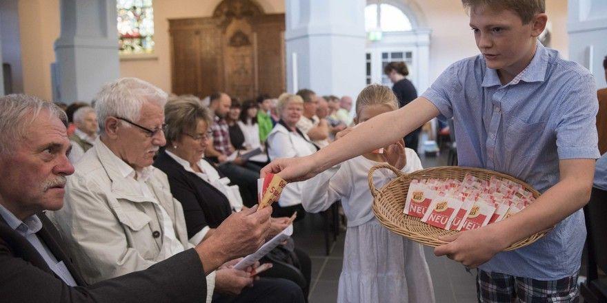 Kinder geben den Besuchern des Eröffnungsgottesdienstes Brot und sammeln Spenden.