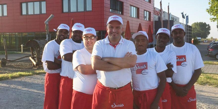 Ulrich Möschl, der Produktionsleiter der Bäckerei Staib, mit sechs der angestellten Migranten aus Ländern, wie Pakistan, Eritrea und Somalia.