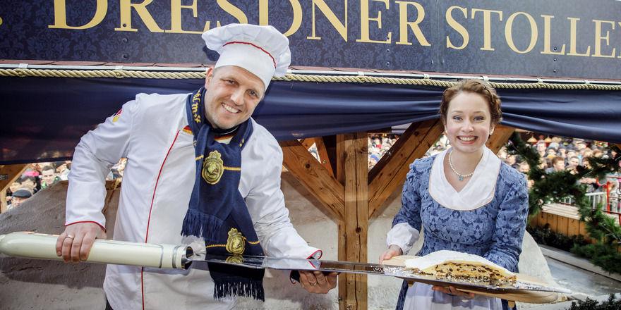 Bäckermeister René Krause und Stollenmädchen Marie Lassig präsentieren ein Stück des Riesenstollens.